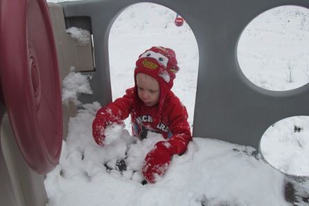 Nathanael is gathering snow for snowballs!
